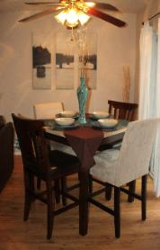 A quaint dining area, with views of the front & back patio, living room & kitchen...